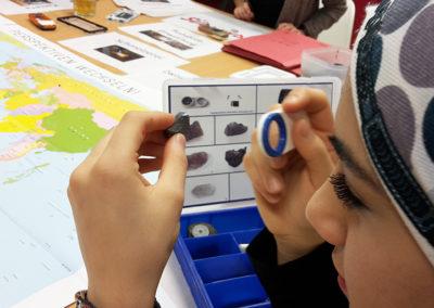 Jugendliche mit Lupe im Workshop