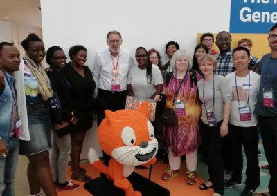Ein Gruppenfoto mit vielen Erwachsenen und dem Maskottchen von Scratch.
