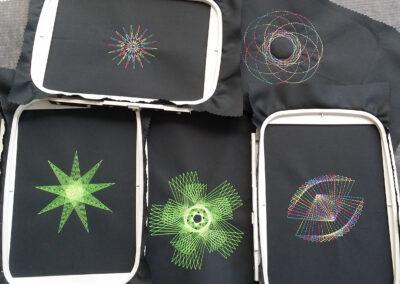 Mehrere symmetrische Stickmuster auf schwarzen Stoffen in Stoffrahmen.